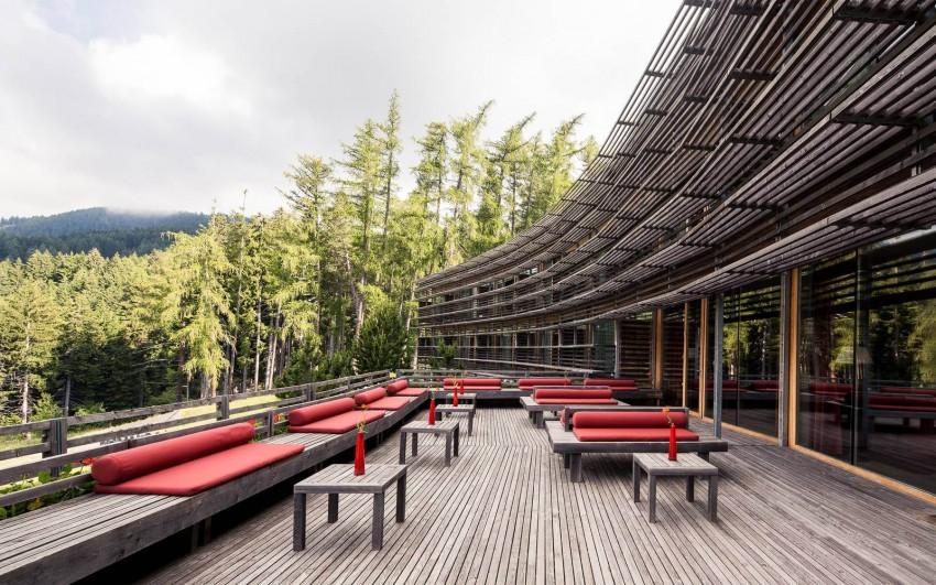 """"""" Eco, não ego!"""" foi o lema do arquiteto Matteo Thun, quando projetou o Vigilius Mountain  Resort, em Itália. Ignorando o supérfluo e concentrando a sua  genialidade no respeito ao  meio ambiente, esta criação em madeira parece ser a extensão natural da floresta Tirolesa.  Aqui o telhado  é coberto com relva e plantas isolantes e as paredes são grandes janelas,  que  deixam  entrar  os  raios  suaves  do  sol  italiano .  O  resultado  são  luminosos  quartos  e  suites, num design elegante e com uma atmosfera tranquila. O cenário ideal para relaxar  no spa ou desfrutar dos deliciosos pratos locais."""
