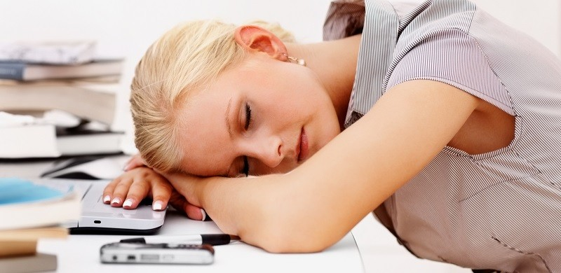 Tired young business woman sleeping while at work