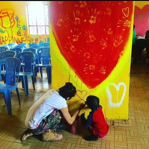 Lourdes Maria a pintar um mural na escola primária