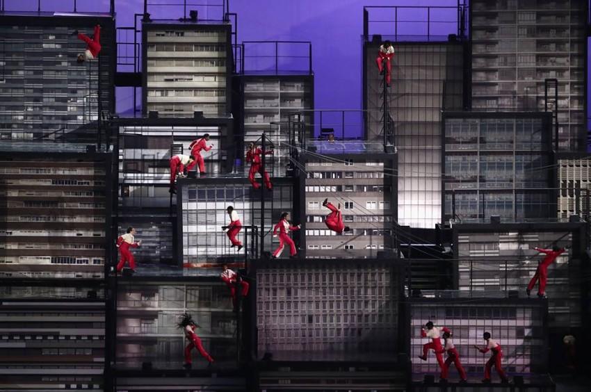 Surge o skyline de uma metrópole brasileira no gigante palco cênico que ocupa uma fatia da platéia do estádio. São quase uma centena de prédios empilhados uns sobre os outros