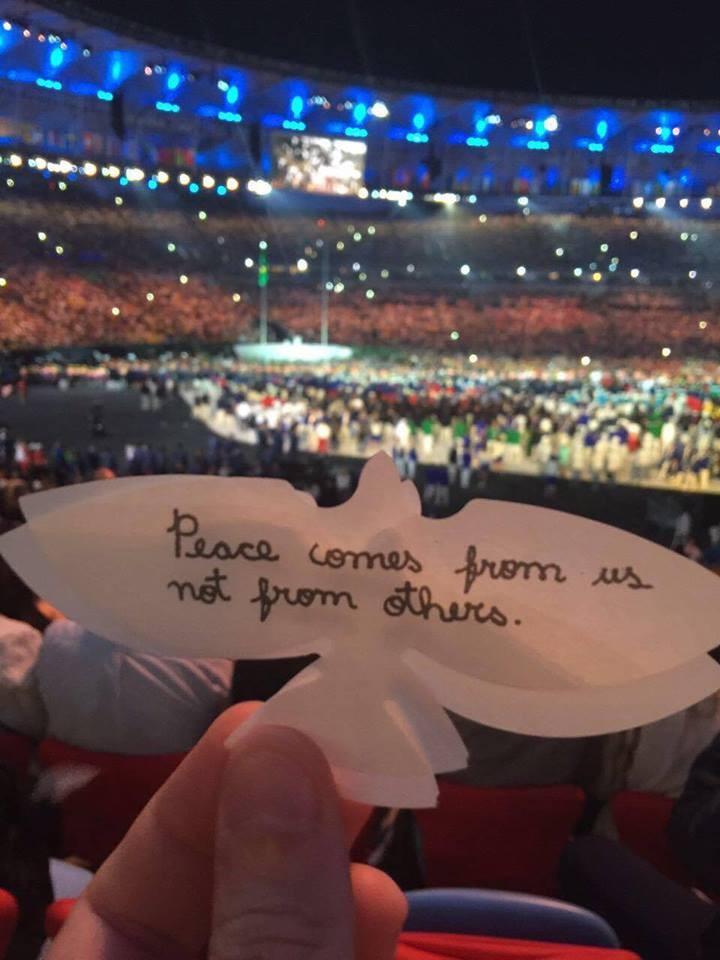 Caem sobre a plateia milhares de pombas de papel, com mensagens escritas pelas crianças do Quénia e do Rio.