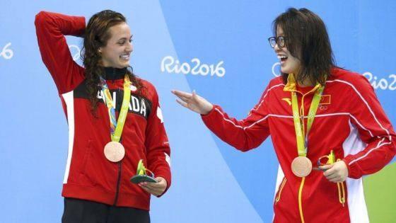 A receber a medalha de bronze nos 100 metros costas