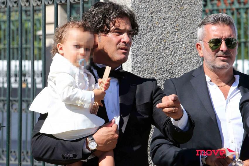 Manuel ao colo do pai depois de ter recebido o sacramento do batismo