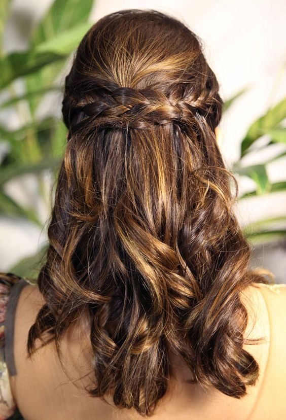 """Trança de Princesa: Separe o cabelo ao meio, pegue uma mecha de tamanho médio de cada lado e faça uma trança. Puxe as duas para trás e entrelace seus fins. Para dar um acabamento mais bonito, passe uma mecha de cabelo fina no meio """"amarrar"""" as tranças."""