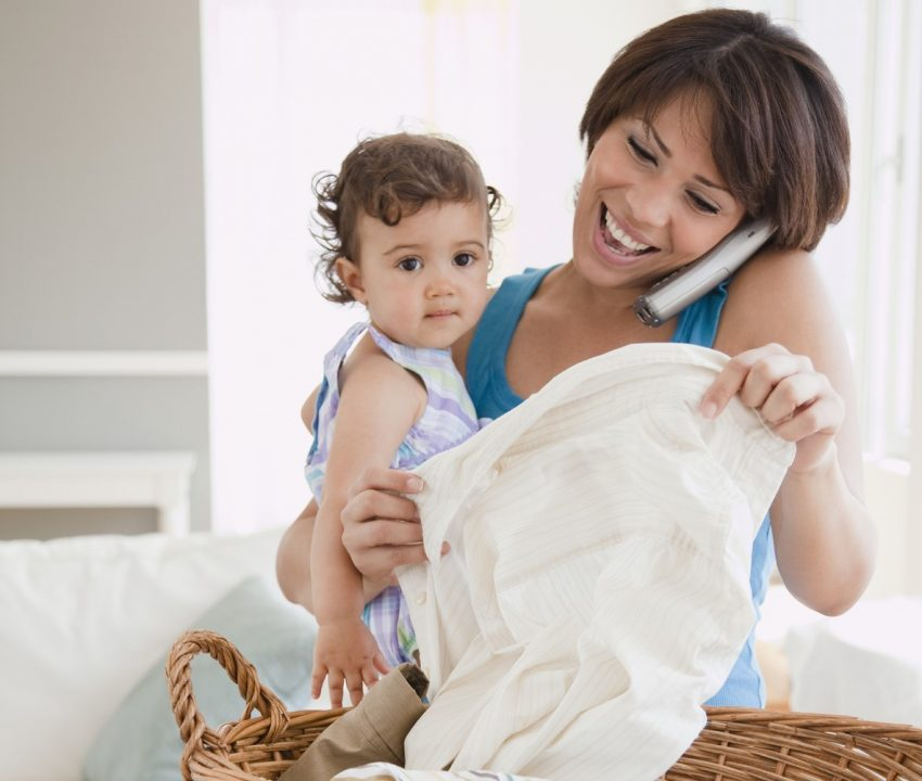 """""""Hispanic mother holding daughter, talking on phone and doing laundry"""""""